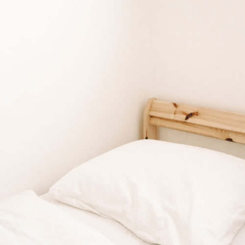 Wooden bed frame with white sheets.
