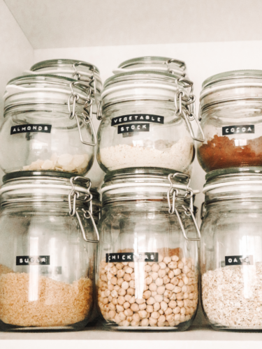 Clear food containers with legumes, oats, sugar.