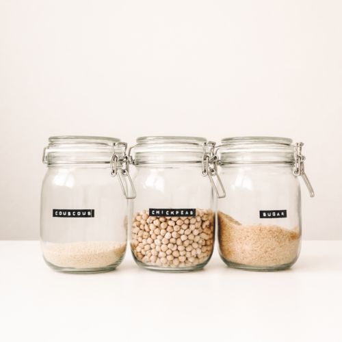 Glass food containers with couscous, chickpeas, and sugar.